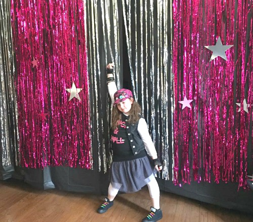 Sleepover Ideas Dance and Doze little girl in dance pose in front of shiny curtains