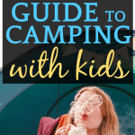 girl camping and blowing bubbles sitting in front of tent