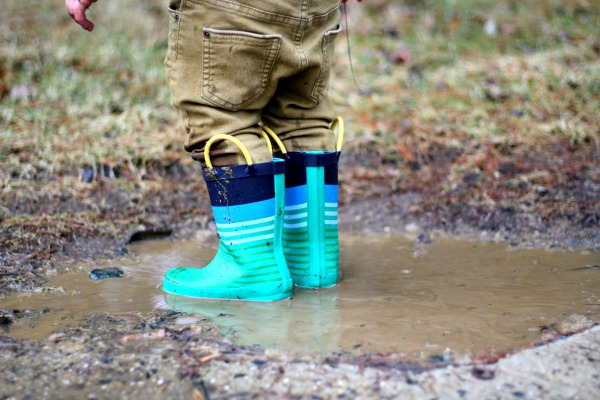 How Homeschooling Is Better for Family child's legs in rain boots stomping in mud puddle