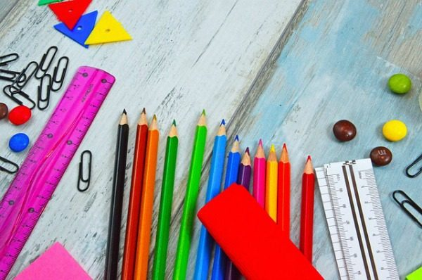 How To Use Back To School Sales to Stock Up for All Year school supplies on table like colored pencils rulers