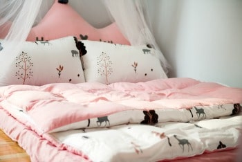 How do you plan a pajama party for kids? a bed with a pink and white comforter