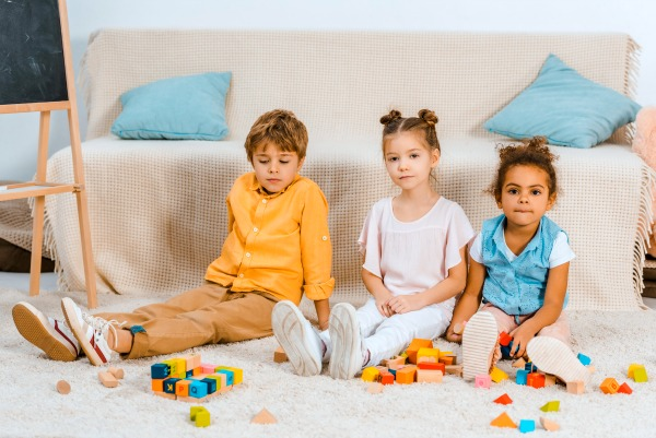 african american little girl and caucasian little girl and caucasian little boy sitting on a carpet playing with colored blocks
