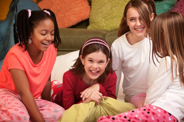 What To Do At A Sleepover For Kids Slumber Party Ideas with 4 tween girls in their pajamas laughing