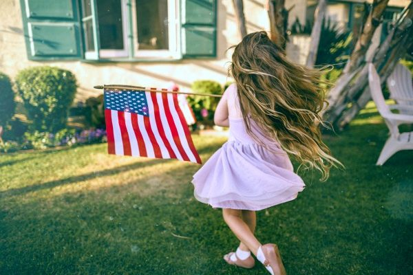What is Independence Day? | 36 Lesson Plans, Activities, Recipes for 4th of July little girl with long hair running in a yard waving an American flag