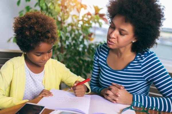 Behind In Homeschool African American mom and child working on home school at a table
