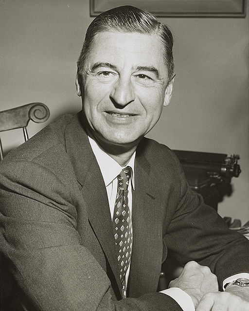 black and white picture of a young Dr. Seuss in a suit and tie with his arms on a desk and smiling into the camera