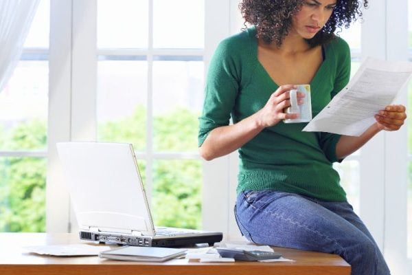 african american mom sitting on a desk and looking confused over a homeschool transcript