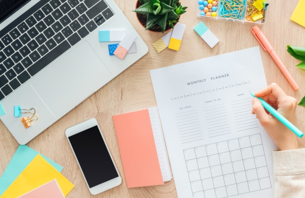 How To Create a Schedule for Homeschooling hand writing on a planner next to a laptop