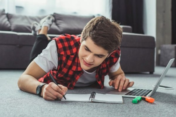 Remote Learning Tips for Parents and students caucasian teen male lying on stomach on floor working on laptop and writing in notebook for a remote learning class