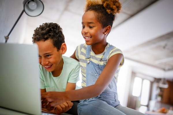 elementary age black girl and boy laughing in front of a laptop while doing a Virtual Scavenger Hunt for Kids