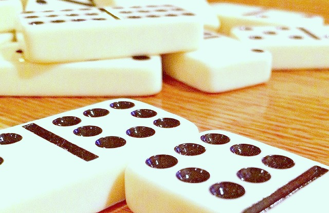 How To Play Dominoes white dominoes with black dots on a top of a table