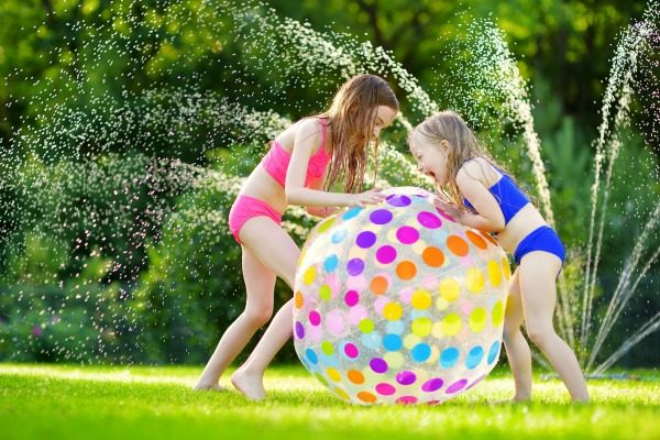 21 Creative Staycation Ideas When Family Vacation Canceled 2 little girls play with a giant blow up beach ball in a sprinkler in a yard