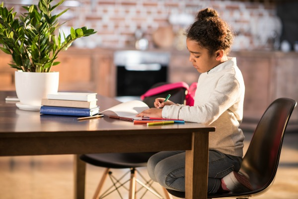 Teach at Home Resources african american girl sitting at the kitchen table and doing homework