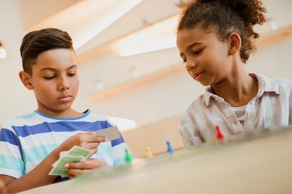 preteen african american boy and preteen teen african american girl sitting at a table and playing Games In Learning with cards and game pieces