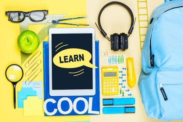 school supplies like pencils tablet calculator backpack sitting on a yellow table