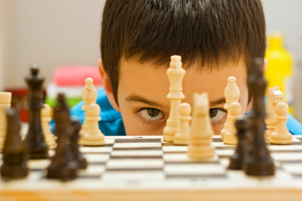 close up of boy's eyes looking through chess pawns into the camera