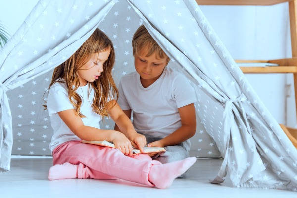 boy and girl sitting under an indoor reading space canopy tent looking at a book