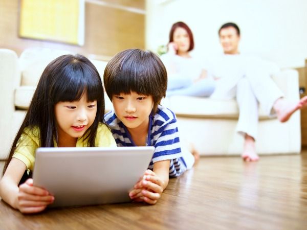 a boy and girl laying on floor and looking at iPad