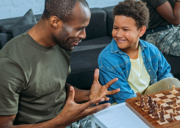 African american dad playing chess with smiling african american boy