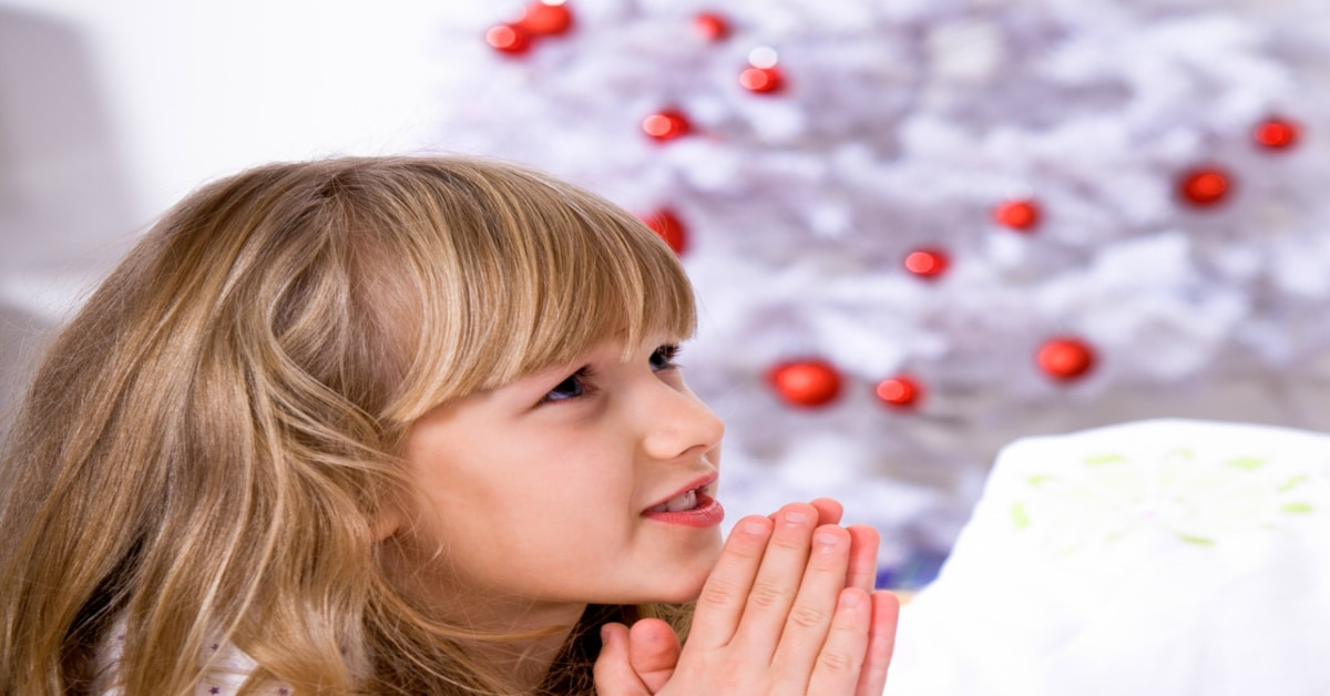 Experience Gifts For Christian Kids child praying in front of white christmas tree
