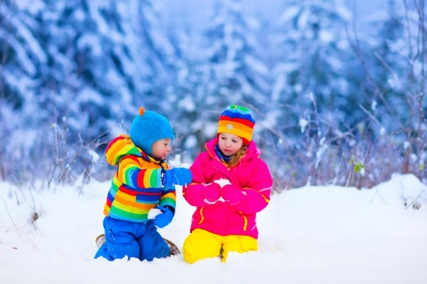 January Activities For Kids with two kids in colorful coats and scarves sitting in the snow