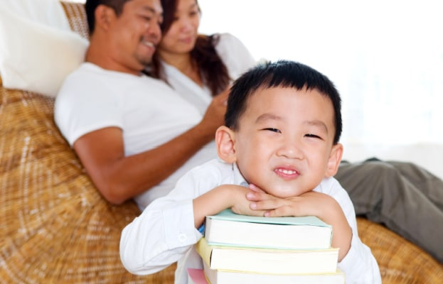 Homeschool How To asian boy with with head on top of a stack of books and smiling with parents smiling in background