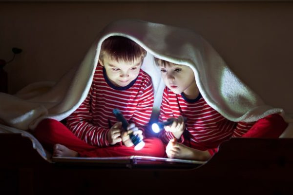 Power Outage Fun With Kids two kids under a blanket in the dark reading a book with flashlights
