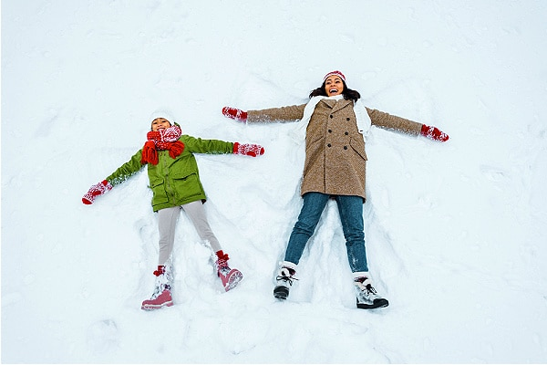 african american mother and daughter making snow angels and fun Snow Day Activities