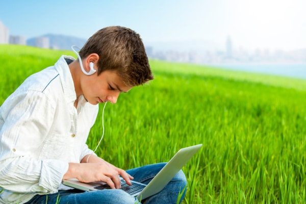 caucasian teen boy working on summer school online on a laptop while sitting in grass outside on a summer day