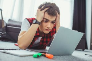 BEHIND IN HOMESCHOOL HIGH SCHOOL teenager high school student stressed working on online high school program