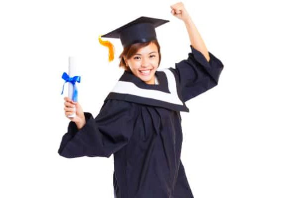 Graduation high school homeschool female high school student jumping up in air with graduation diploma in hand