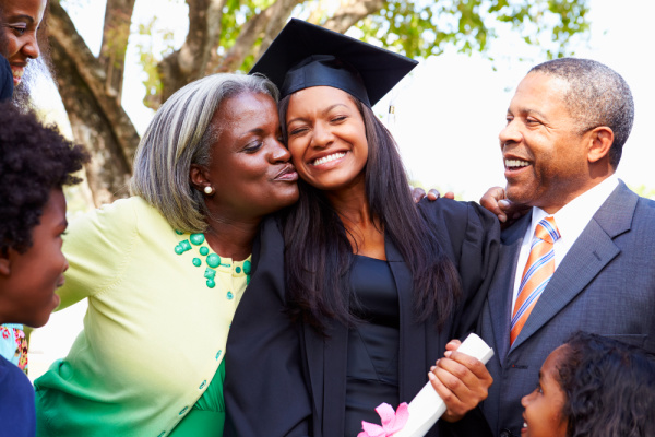 Homeschooling for High School black family laughing around a homeschool graduate daughter holding her diploma