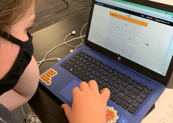 The Juice Homeschool review with homeschooler reading current events on the homeschool program