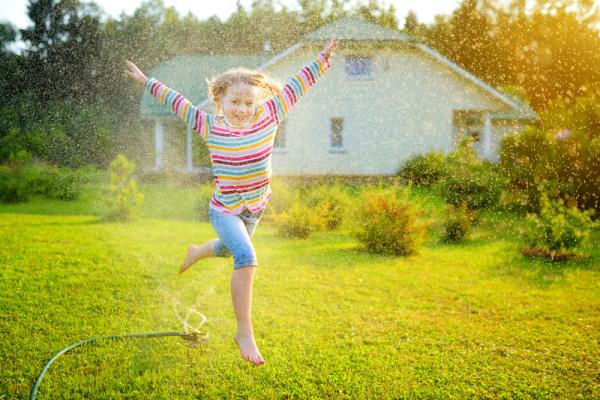girl running through sprinkler for Best Backyard Water Fun in summer