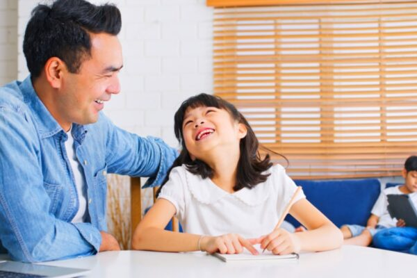 Back To School For Homeschool father helping a happy homeschooled student daughter at table