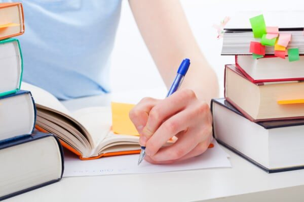 How To Prepare for Homeschooling hands writing notes with homeschool books around on a table