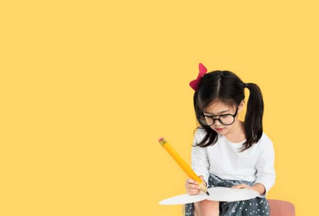 New Homeschool Year young homeschooling girl with long dark pigtails writing with an oversized homeschool pencil