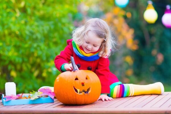 preschool activities for Halloween little girl sitting on a table outside looking at a jackolantern