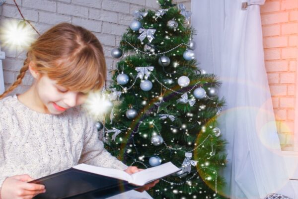 Christmas Present Ideas For Readers little girl smiling while reading in front of Christmas tree
