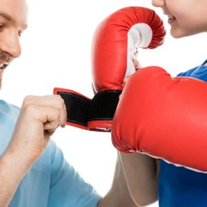 photo of a father helping son put on boxing gloves