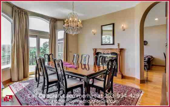 The elegant dining room in this waterfront home for sale in CT has walls of windows overlooking the pool and the breathtaking views.