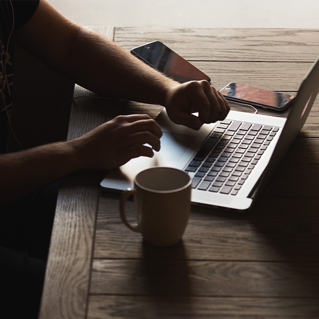 Hand shot of a man using laptop with coffee on wood table