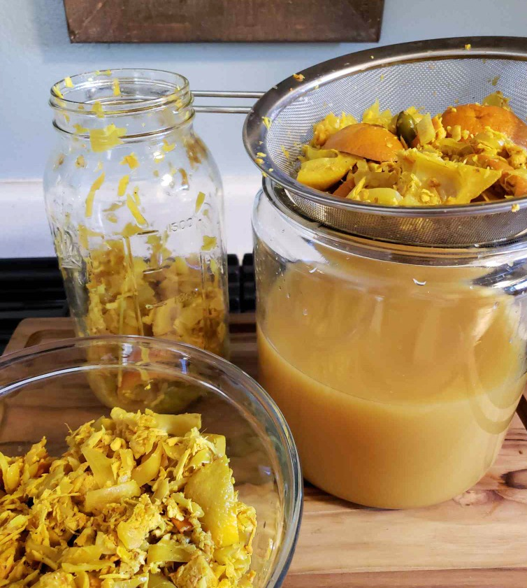 Straining and separating the herbs, turmeric, ginger, onions, and other solid bits from the rest of the liquid. The contents of the jar are poured through a fine mesh metal strainer into a large glass crock below, which catches the fire cider liquid.
