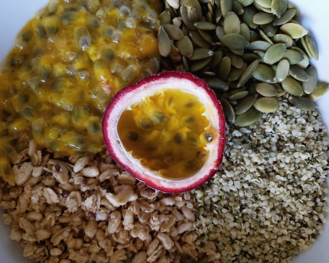 A vegan breakfast bowl full of pumpkin seed, flax seed granola, raw pumpkin seeds, and hemp hearts, all known to be high in omega-3 fatty acids, with homegrown passionfruit