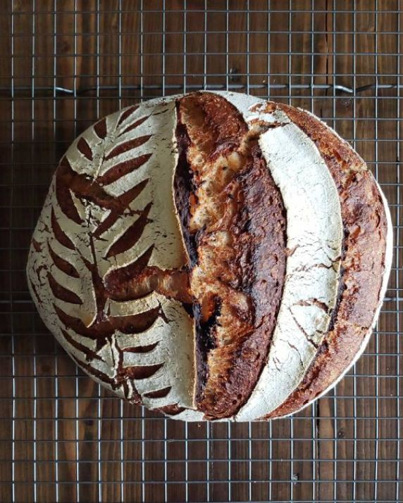 A loaf of fresh-baked homemade sourdough, still sitting on a cooling rack. The loaf has a nice decorative, floury crust that has been scored with leaf patterns using a bread lame.