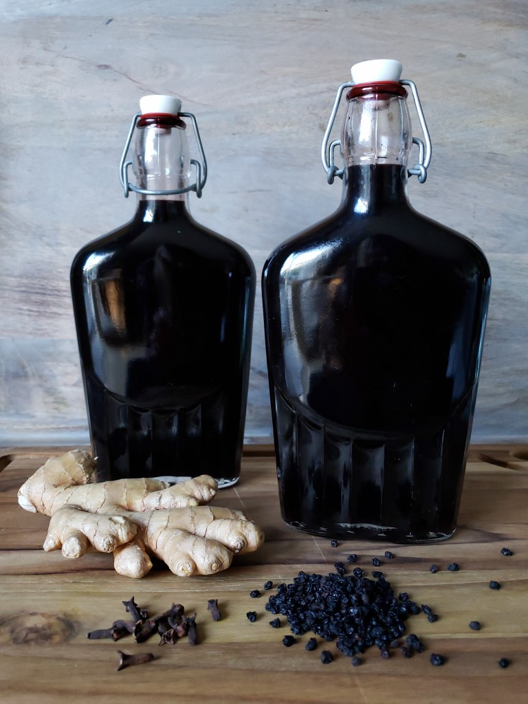 Two full swing-top bottles of dark, inky, nearly black homemade elderberry syrup. In the foreground lays a hand of ginger and randomly spilled dried elderberries around the base of the bottles.