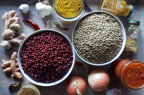 A photo of all the ingredients to make madras curry lentils. Two white bowls are full of red adzuki beans and green lentils, with onions, chillis, garlic, turmeric, ginger, and spices laying around the sides of the bowls