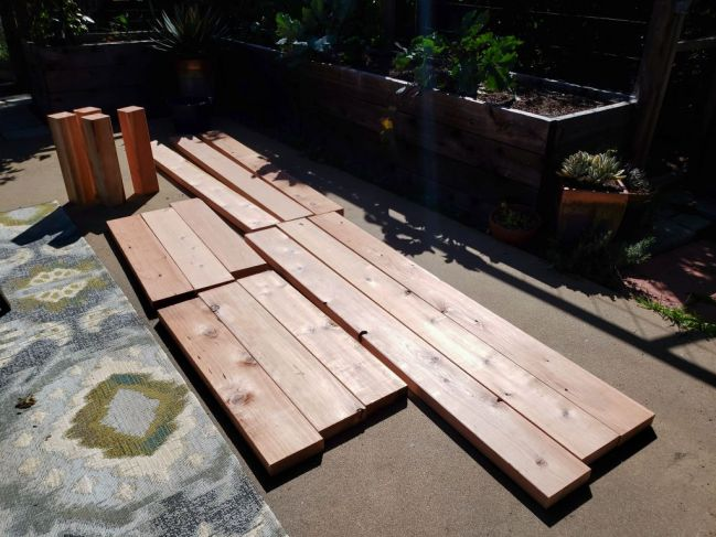 An image of a dozen cut redwood boards laying on a concrete patio, waiting to be put together into a raised bed.