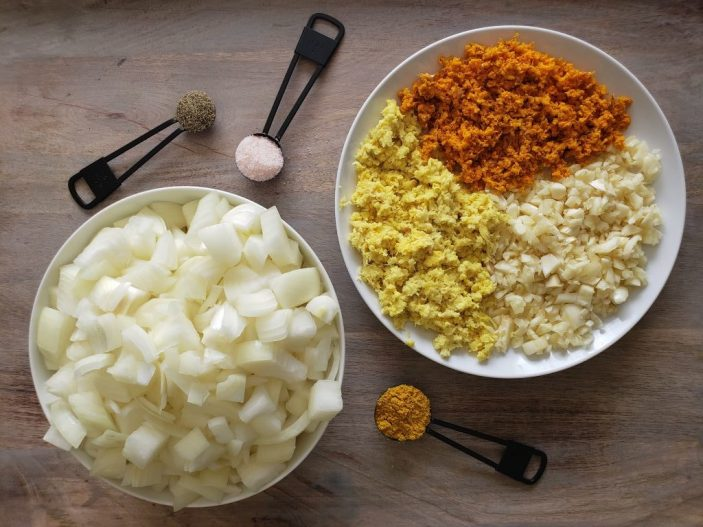 """The """"wellness trifecta"""" of turmeric, ginger, and garlic are all chopped up on a plate on the right. Diced onions are piled in a bowl on the left. Around the plate and bowl, measuring spoons full of turmeric powder, black pepper, and salt are sitting."""