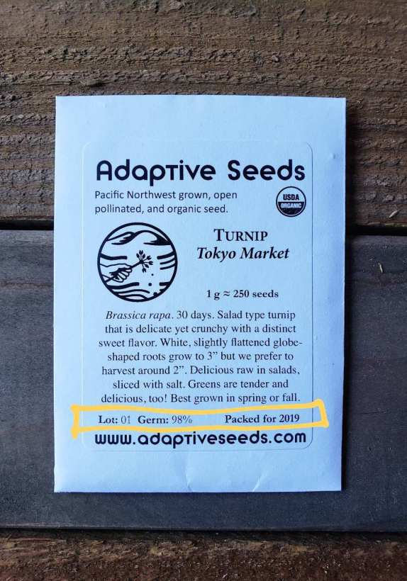 """A close up image of a seed pack from Adaptive seeds, the package is white with black writing and logo. The seed pack is a type of turnip labeled Tokyo Market. There is a description of the vegetable saying that it is a """"salad type turnip that is delicate yet crunchy with distinct sweet flavor."""" The author of the article has highlighted part of the pack which tells that the seed pack has a 98% germination rate and it is packed for 2019."""